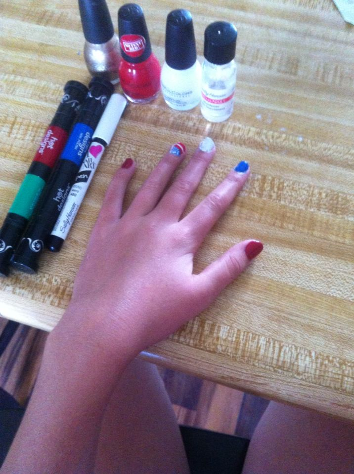 This design is for kids or adults!  1. You put on the red, white and blue on all nails but the accent nail. 2. Do a white coat on your accent nail.  3. After all your nails are dry do a second coat on all of your nails including the accent nail.  4. On your accent nail diagonally paint a blue line with your nail pen and fill in the top half blue.  5. Then with your red nail pen do the first line blue then leave a space and then do a red line again until your done.  6. On all nails apply top…