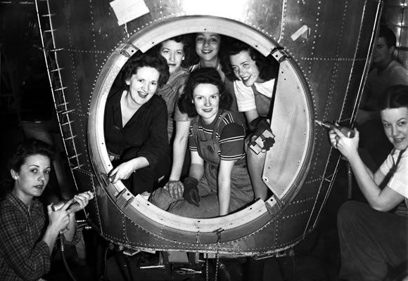 """World War II """"Rosie the Riveter"""" airplane builders pose for photo with aircraft in factory. Photo courtesy of the Museum of History and Industry, Seattle."""