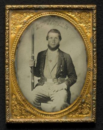 An ambrotype photograph of a seated Civil War soldier (corporal Tiller; 6th Fla. Infantry Regt.) holding an upright musket in his left hand, his right hand rests on his thigh. He has an under the chin beard, is wearing what appears to be a tail coat with a military belt, an open shirt and a stock or perhaps undershirt.