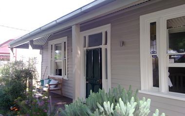 The weatherboards are 'Linseed' and the windows are 'Ecru 1/4 strength'