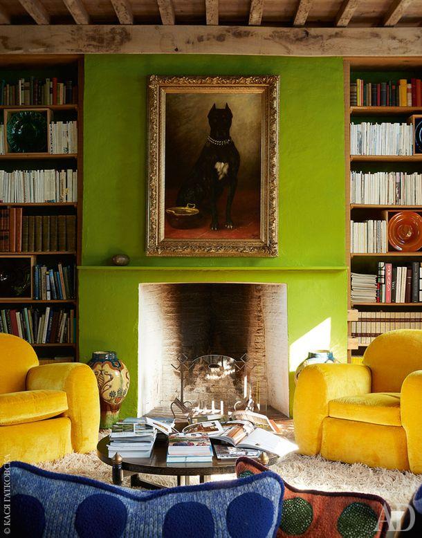 """В библиотеке пара кресел в стиле бельгийского ар-деко. На переднем плане подушки по дизайну хозяина дома. Над каминной полкой портрет датского дога, озаглавленный """"Деклерк"""" и написанный в 1910-е годы."""