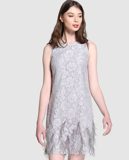 Vestido corto, realizado en encaje en color gris con adorno de plumas. Tiene manga sisa, escote redondo y botón superior en la espalda dejando abertura.