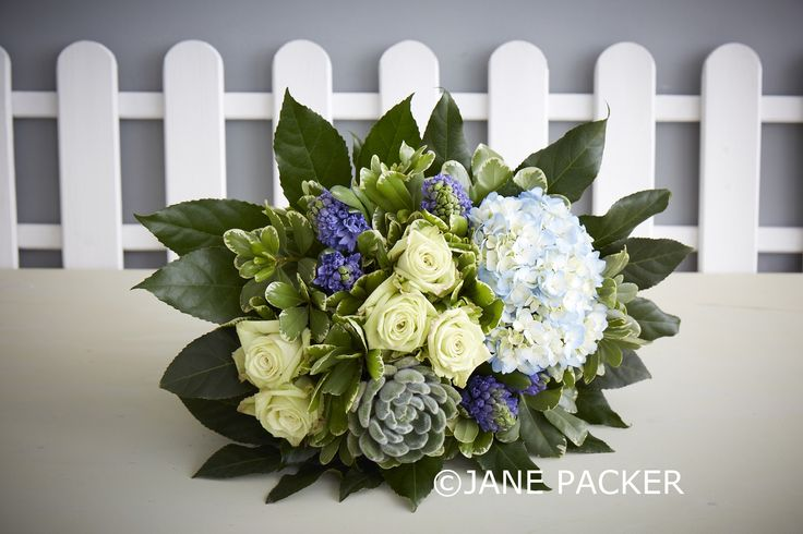 Zingy lime Roses, lovely lapis blue Hyacinth bulbs, a sky blue Hydrangea, a furry little Succulent plant (which can be kept and replanted) along with an abundance of glossy Pittosporum foliage and a collar of spikey greenery make this a truly show stopping arrangement. The green and blue tones make it the perfect gift to celebrate the arrival of a baby boy.