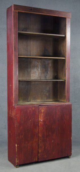 """Pine. One-board sides. Open top above primitive single-board door. Evidence of constant use with wear and staining. With alterations and later red surface. 75"""" x 35"""" x 13""""."""