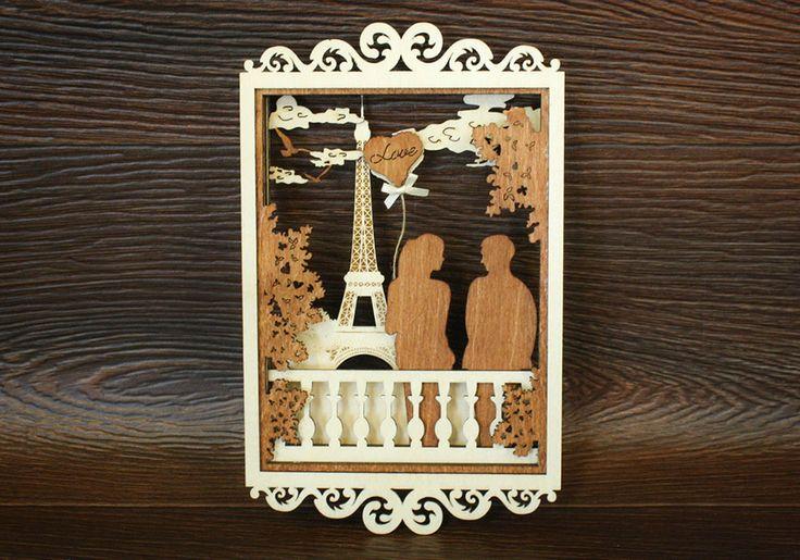 Объемная картина «Любовь в Париже» малая выполнена из нескольких слоев березовой фанеры. Окрашена морилкой по дереву. Высота 23,5 см, ширина 14,5 см. Вешается на стену с помощью потайной ленточки. На картине изображена влюбленная пара гуляющая на мосту на фоне Эйфелевой башни. У девушки в руках воздушный шарик в виде сердечка с надписью Love. Шарик украшен маленьким бантиком из атласной ленты.