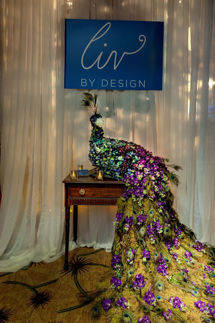 A peacock made entirely of dark purple and dark blue hydrangeas with a cascading tail of moss, peacock feathers and purple stock flowers will be the show-stopper to the reception and will be placed on a table near the entrance of Ballroom.