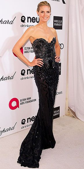 All the Afterparty Dresses, from Pretty to Plunging | HEIDI KLUM | The theme of the Oscars was heroes, and between the superhero-esque bodice of her black gown and the heroic effort she's making to not wince at the boob squishing going on, Heidi clearly made an appropriate choice for the Elton John AIDS Foundation viewing party.