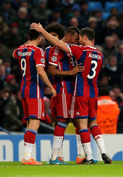 Robert Lewandowski (L) of Bayern Muenchen is congratulated by teammates after scoring his team's second goal during the UEFA Champions League Group E match between Manchester City and FC Bayern Muenchen at the Ethad Stadium on November 25, 2014 in Manchester, United Kingdom.
