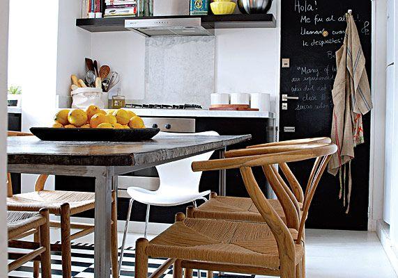 Realizado con marcador, es un auténtico work in progress que Martina va completando poco a poco. A su lado, la mesa lleva sillas clásicas (la Wishbone de Hans Wegner y las de la Serie 7 de Arne Jacobsen), está iluminada por dos lámparas de alambre compradas en Roma y se posa sobre una original alfombra trompe l'oeil (foto 2) trazada con pintura epoxi directamente sobre el piso de cemento. En la pared del fondo conviven la cocina y la puerta de servicio transformada en pizarrón.