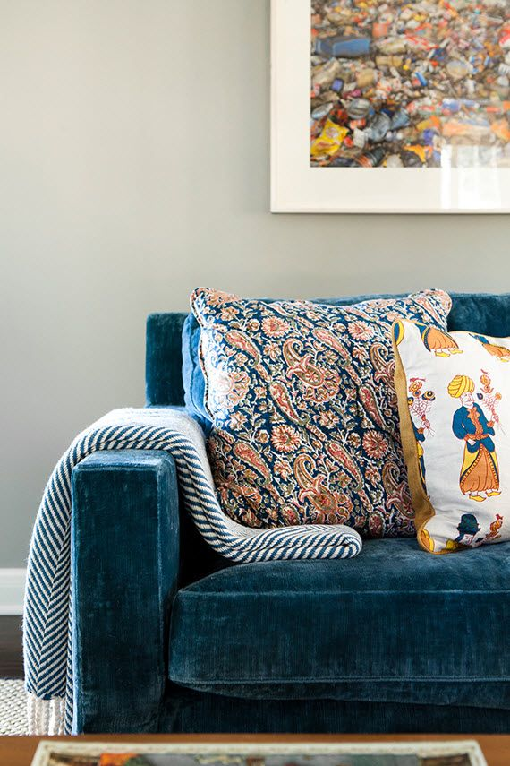Glamourous prussian blue velvet sofa softened with folky Indian Block print cushions in warm terracotta and sunshine yellow.