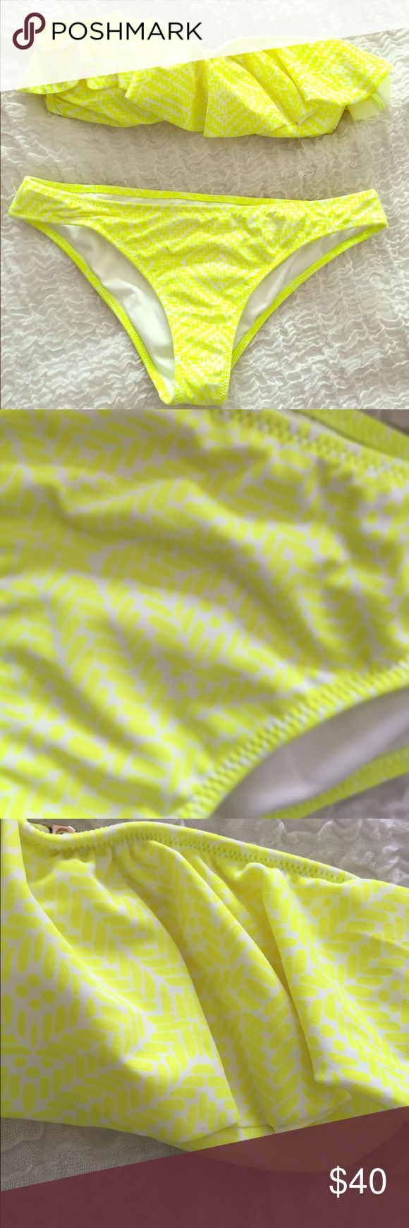 Victoria's Secret bandeau bikini Victoria's Secret size small bandeau bikini. Neon yellow with white geometric print - the print is very subtle. The top has removable padding, clasps at the back, and has a ruffle flounce top. The bottoms are the cheeky style. This has only been worn once and has a very small mark on the top (see last photo) but it is hidden by the ruffle overlay. Victoria's Secret Swim Bikinis