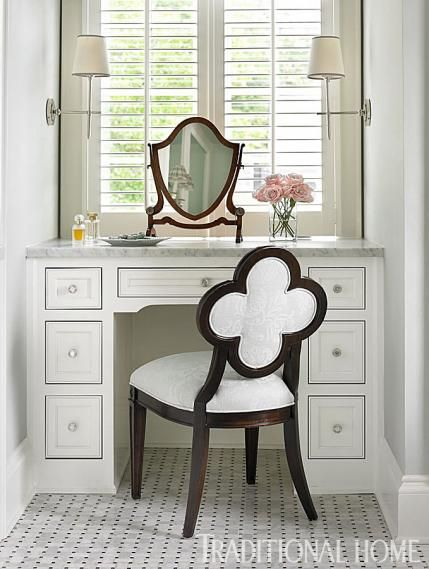 A quatrefoil-back chair by Suzanne Kasler for Hickory Chair cozies up to the bathroom's built-in vanity. - Traditional Home ® / Photo: Emily Jenkins Followill / Design: Lauren DeLoach