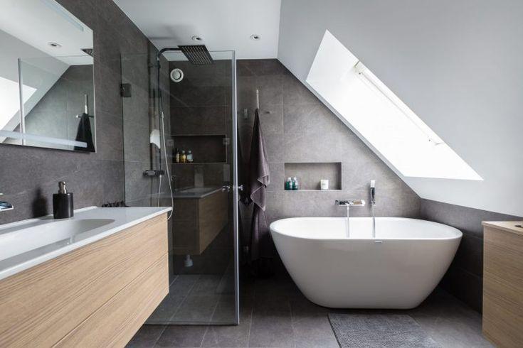 Grå skifferplattor på både väggar och golv. Under ett stort fönster i snedtaket står ett runt, fristående badkar med handdusch och förvaringsnisch. I badrummet finns även en dusch med takdusch och två glasdörrar, även den med en nisch för badrumsartiklar. Ett större vägghängt handfat med ett underrede i ljust trä kombineras med ett vägghängt badrumsskåp i samma serie. Alla rör i badrummet är infällda.