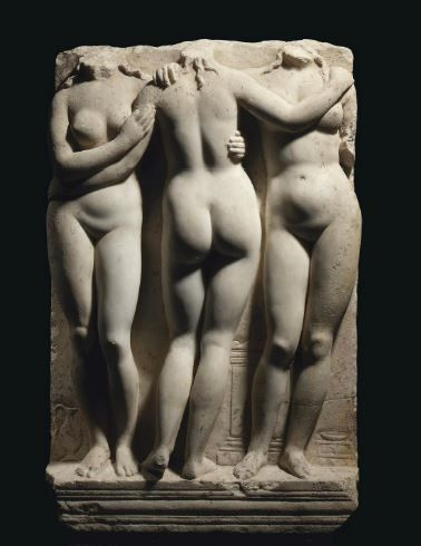Roman marble relief of the Three Graces, 2nd century A.D. The middle figure with weight on right leg, left leg bent at knee with slight twist to her body, the figure on the right with her right arm resting on shoulder of middle figure, each figure with tendrils of hair falling onto shoulders, in low relief behind are an oinochoe, altar and low stool with phiale, 68.6 cm high. Private collection