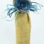 Jutowy worek na wino z niebiesko-szarym kwiatem, wiązany rafią.   Burlap wine bag with blue-grey fabric flower.