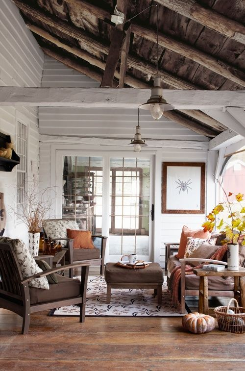 Bright and charming cabin living room with shiplap walls, exposed beams in the vaulted ceiling and plenty of fall decor.