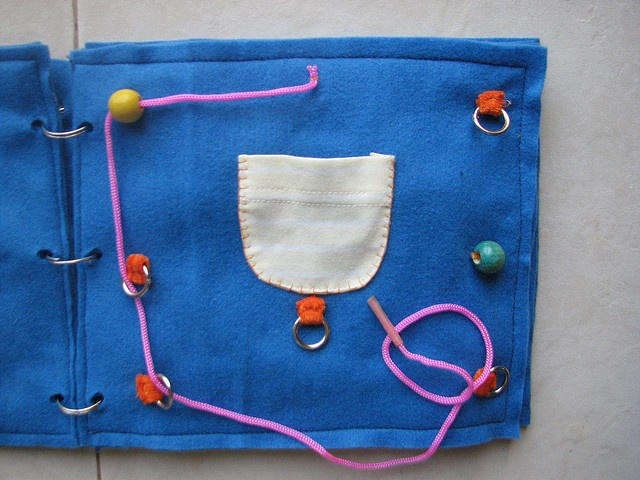 Threading idea for a Quiet Book.  This link has another couple of good ideas, too.  Love the felt dress up doll..