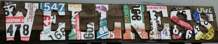 Running bibs modge podged around letters, mounted on pallet boards