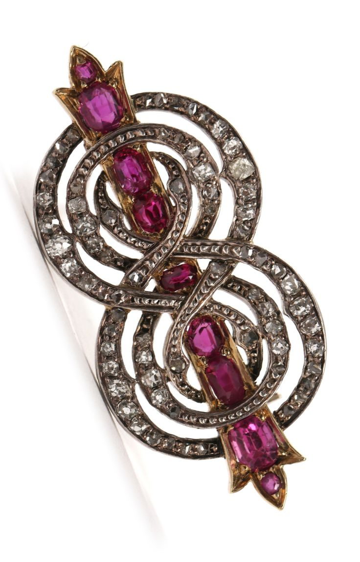 An antique ruby and diamond brooch, late 19th century. Set with nine round- and oval-cut rubies and numerous old- and rose-cut diamonds, mounted in 14k gold and silver.