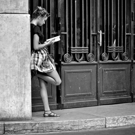 Chica leyendo al lado de un antiguo portal
