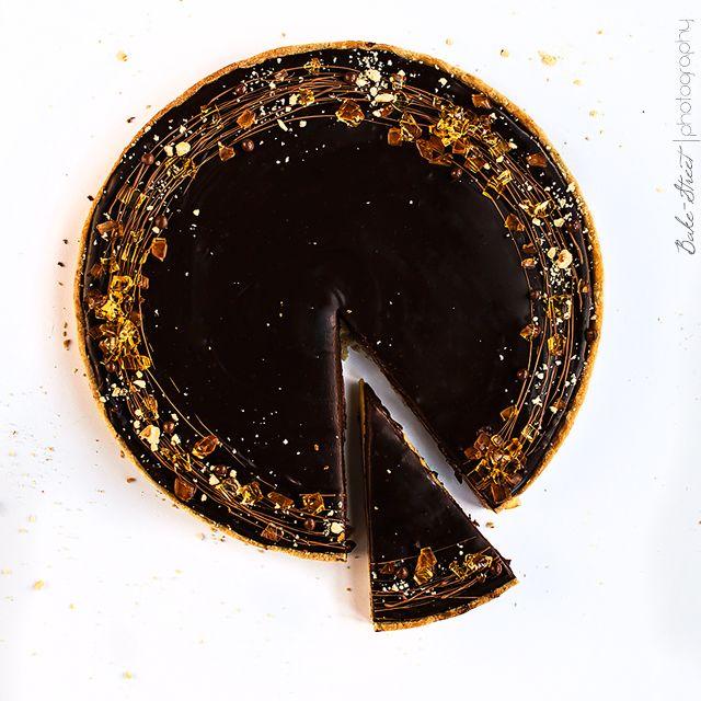 """Tarta de caramelo y ámbar, una pâte sucrée de avellanas con relleno cremoso de caramelo, cobertura de chocolate negro y decorado con """"ámbar"""" de caramelo."""
