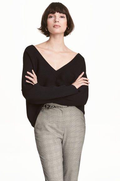 Camisola em malha canelada: Camisola larga em malha canelada de mistura de viscose com brilho. Modelo com decote em V e mangas compridas.