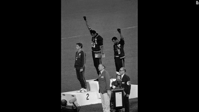 American athletes Tommie Smith, center, and John Carlos raise their fists and hang their heads while the U.S. national anthem plays during their medal ceremony at the 1968 Summer Olympics in Mexico City.