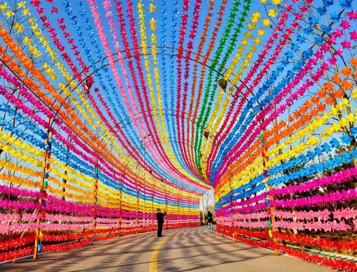 Homme se tenant au milieu d'une route décorée de petits moulins à vent colorés pour le «Pinwheel and Kite Festival» à Tangshan (Chine).