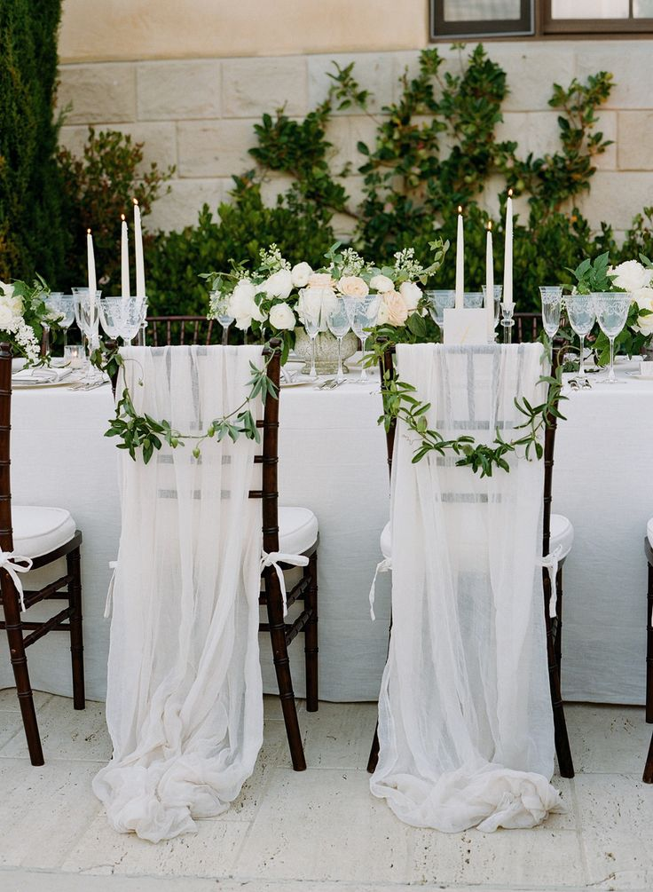 romantic tulle draped onto the chairs for the bride and groom.