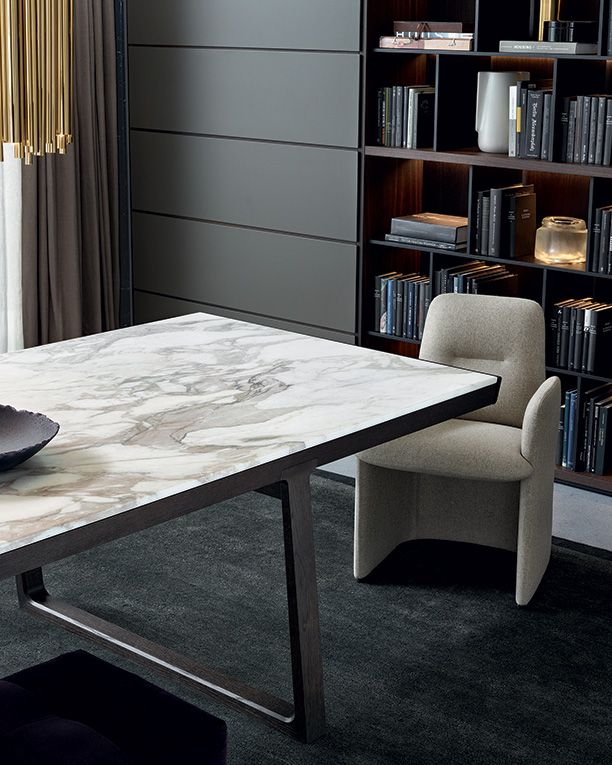 """Guest chairs covered in 8 avorio Norway removable fabric. Opera fixed table, structure in spessart oak, top in mat Calacatta oro marble. Wall system in spessart oak, Slim doors visone mat lacquered, grid th. 1/2"""" carbone mat lacquered."""