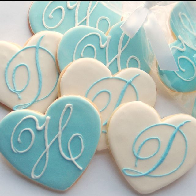 Monogrammed wedding cookies for favors! It would be cool if some of them could be crosses as well as hearts!
