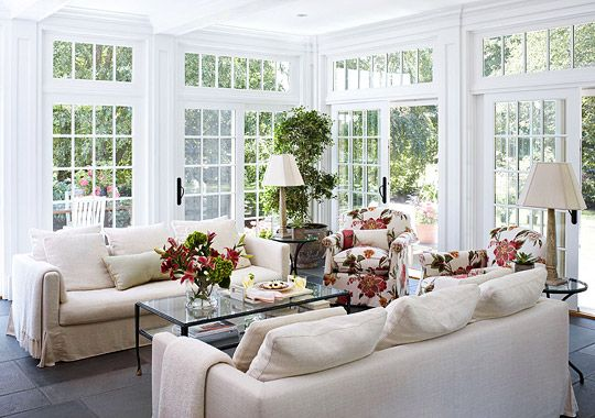 Three walls of sliding glass doors help illuminate the light, bright sunroom. - Traditional Home ®/ Photo: Werner Straube / Design: Patricia Sarnataro