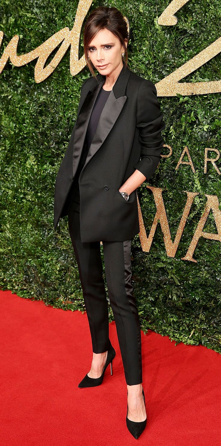 Victoria Beckham delivered another one of her impeccable looks as she hit the 2015 British Fashion Awards in sleek black tuxedo suit separates with satin lapels and stripes down each leg. She styled them with a simple black top underneath and black pumps.
