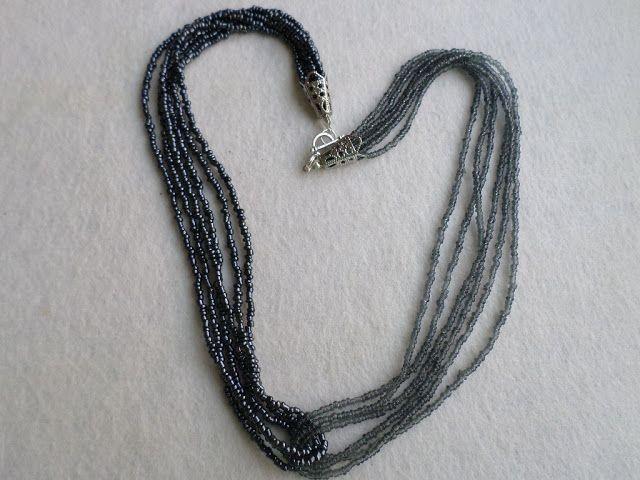 SERIE LIMITATA  (5 bucati/combinatie).  Colierele Ombra sunt facute in serie limitata, din doua bucle a cate trei siruri de margele de nisip de 2 mm, in doua nuante ale aceleiasi culori.   Aceasta este varianta in doua nuante de negru.  Colier handmade, simplu, elegant si diafan, din margele de nisip de 2 mm, in nuante de fumuriu si negru-hematit.  Se inchide cu togle argintiu. Lungime 54 cm.