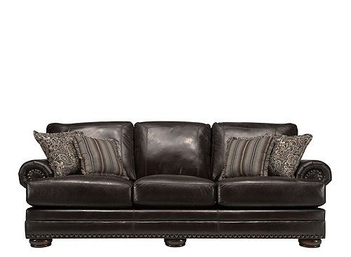 With a leather look and suede feel, this Burgess sofa is hard to resist! Its classic styling boasts the elegant details traditional decorators are searching for, like pleated roll arms, bun feet, topstitching and nailhead trim. Plus, the beautiful fringed accent pillows suit this sofa perfectly, offering design versatility while complementing its rich, old-world style. $799.95