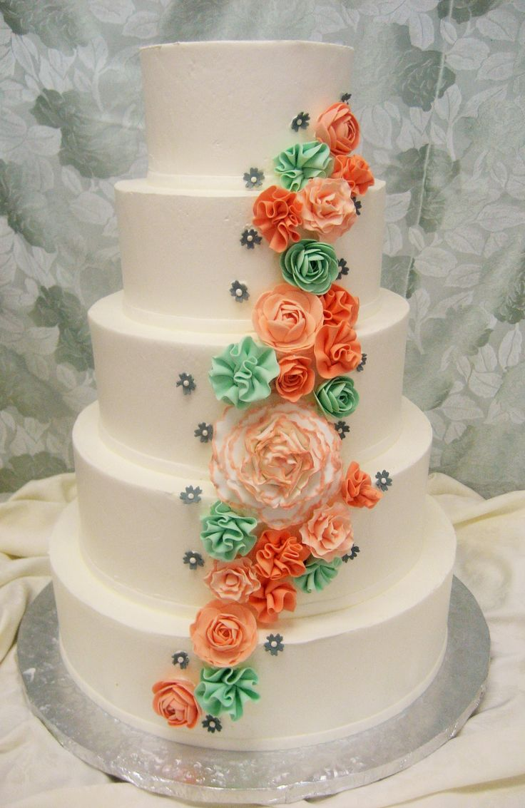 Amelia wedding cake design. Smooth buttercream frosting. Mint, coral and peach fondant flowers. Ruffle flowers. Petal flowers.
