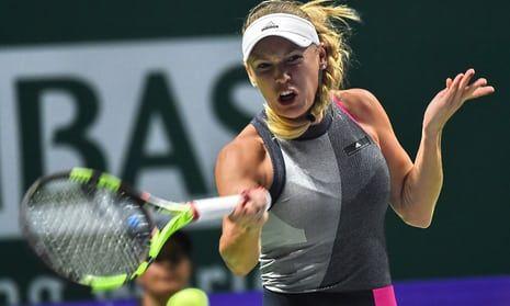 Caroline Wozniacki hits a return against Simona Halep in Singapore.