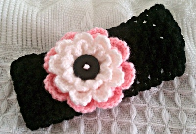 $12 Baby Girl crochet flower headband in colors black, pink, and white.   The band is adjustable, with 2 buttons to make smaller or larger band. The band measures from 12-inches long at its smallest and 14-inches long at its longest, depending on the button used to close it. The large flower embellishing this band measures 3-inches. It fits baby's head as small as about 14-inches in circumference. Baby girls from 0-12mos.