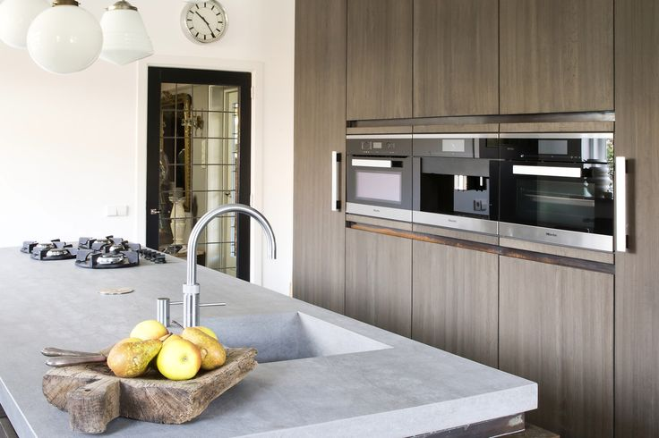 Een keuken met strakke lijnen, bijzondere materialen, sprekend contrast met de historische locatie en mooie accenten van koper.