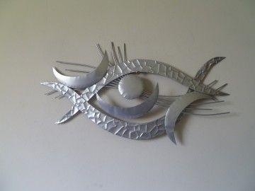 Een zilverkleurige metalen wanddecoratie.De wanddecoratie heeft een moderne uitstraling en past ook het beste in een modern interieur.
