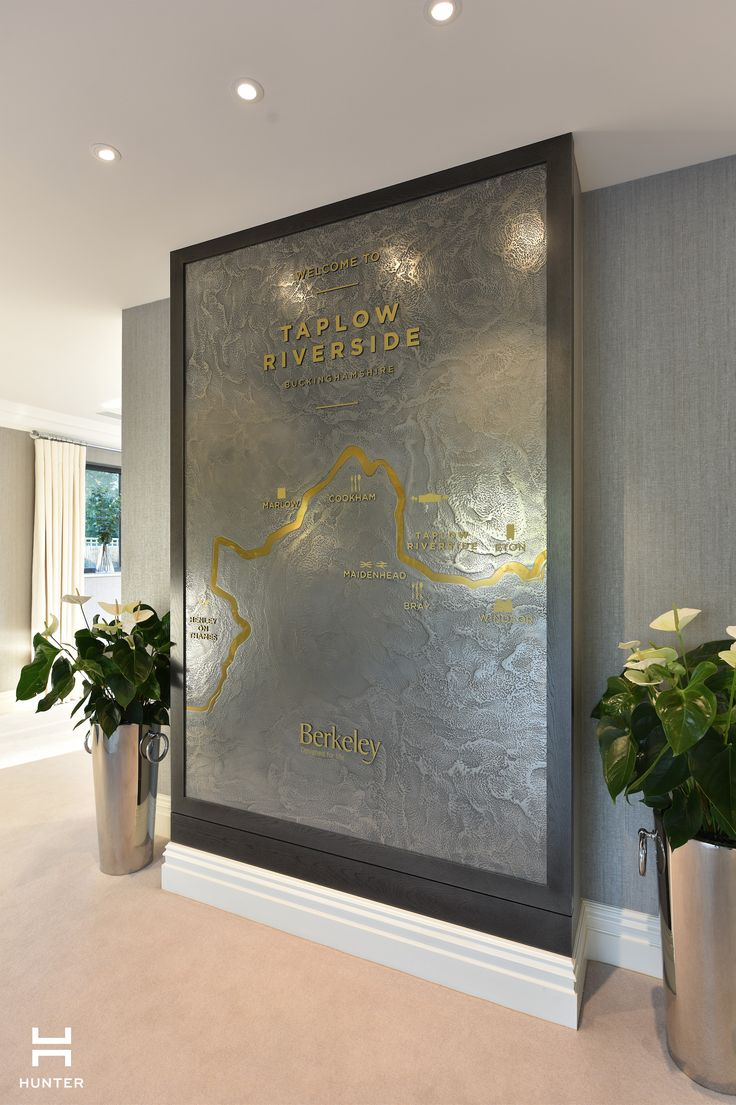 Taplow Riverside Marketing Suite www.hunter-design.co.uk  Feature wall in pewter metal with polished gold river detail running through.  Panel designed and commisioned by Hunter.