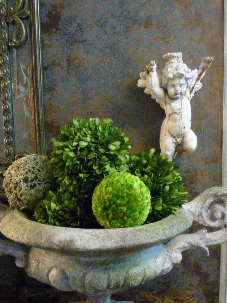 vintage urn with boxwood balls and a cherub....