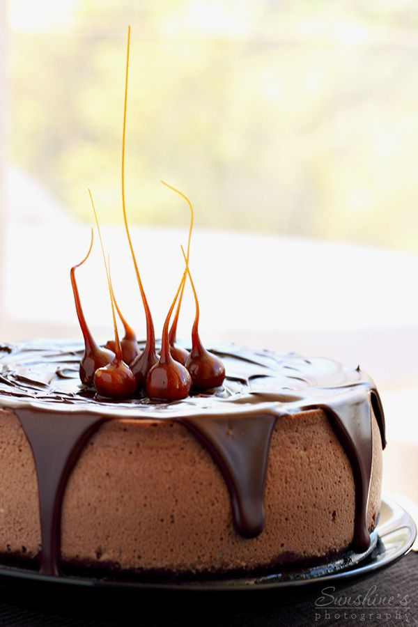 Chocolate and hazelnut cheesecake. To finish the cheesecake, melt chocolate and heavy cream together and stir until they are smooth. Pour over the cooled cheesecake and decorate with caramelized hazelnuts.