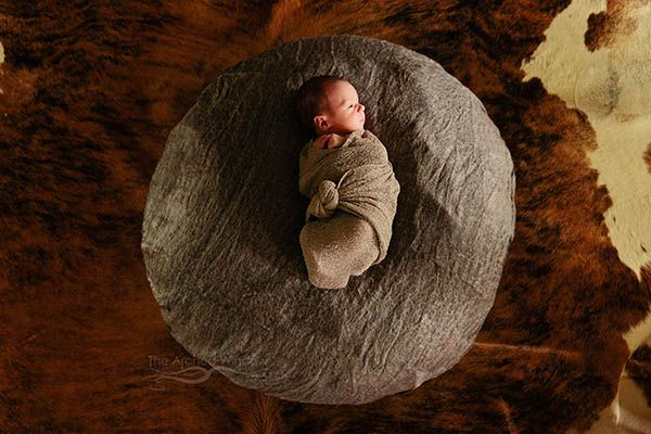 newborn on cowhide blanket country photoshoot