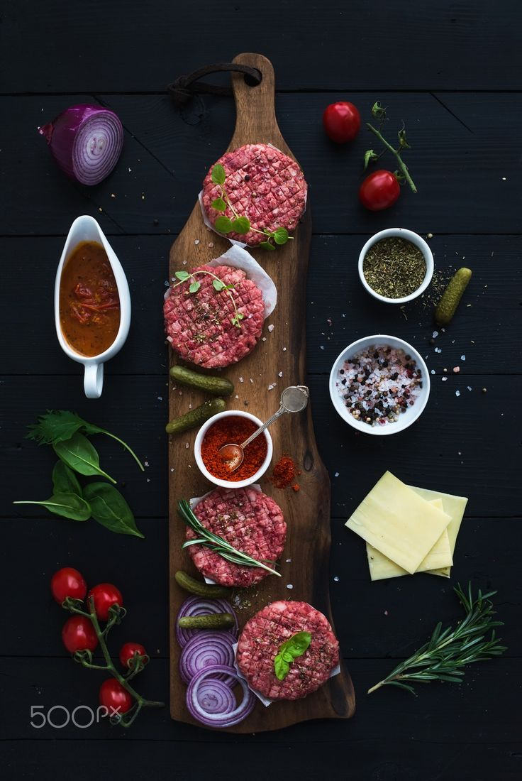Ingredients for cooking burgers. Raw ground beef meat cutlets on wooden chopping board, red onion, c - Ingredients for cooking burgers. Raw ground beef meat cutlets on wooden chopping board, red onion, cherry tomatoes, greens, pickles, tomato sauce, cheese, herbs and spices over black background, top view