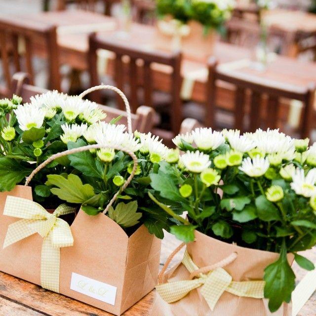 chrysanten in hippe tasjes met strik als decoratie op de dinertafel