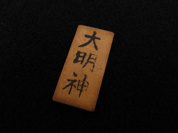 """Wooden Japanese charm recovered from a Japanese soldier's uniform in the Pacific during WWII. The characters have been translated as """"Daimyjin,"""" the name of a Shinto god, so this is most likely a good luck charm (omamori). From the collection of the Air Force Museum of New Zealand."""