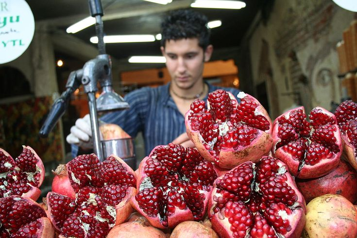 A worker preparing fresh pomegranate juice from these pomegranate fruit. Photo taken at a market in Istanbul, Turkey.