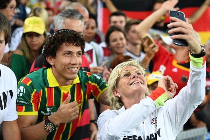 Germany's coach Silvia Neid poses for selfie photographs with fans following the Rio 2016 Olympic Games women's football Gold medal final match at the Maracana stadium in Rio de Janeiro, Brazil, on August 19, 2016..Germany won the match. / AFP / Luis Acosta
