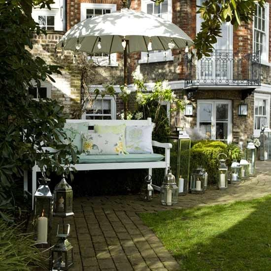 For an elegant garden setting whatever the occasion, use lighting along a path to lead guests to a relaxed seating area. Layer a country-style bench with comfy cushions in pretty floral fabrics and keep the area shaded with a decorative parasol.